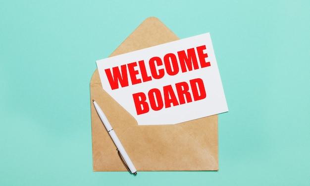 水色の背景には、開いたクラフト封筒、白いペン、「ようこそボード」というテキストが書かれた白い紙があります。