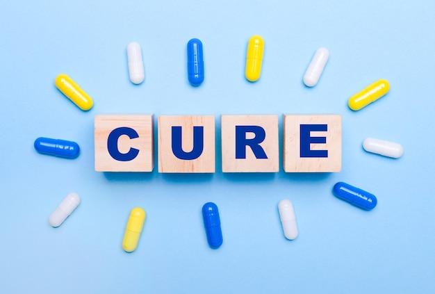 水色の背景に、色とりどりの丸薬と木製の立方体に「cure」というテキストが表示されます。医療コンセプト