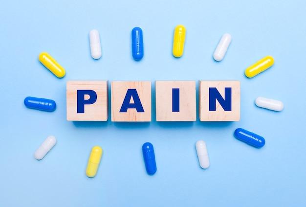 На голубом фоне разноцветные таблетки и деревянные кубики с текстом боль. медицинская концепция
