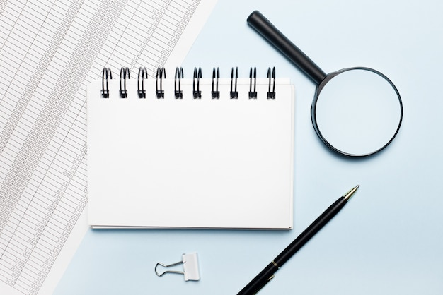 水色の背景に、レポート、虫眼鏡、ペン、テキストやイラストを挿入する場所のあるノート。ビジネスコンセプト。フラットレイ。テンプレート