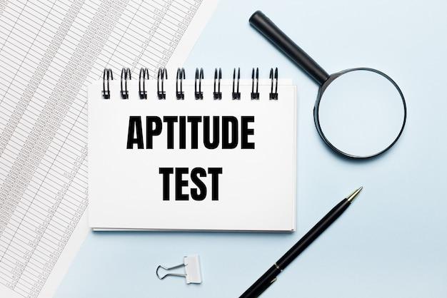 水色の背景に、レポート、虫眼鏡、ペン、およびaptitudetestというテキストが記載されたノートブック。ビジネスコンセプト。フラットレイ。