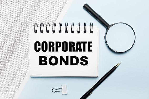 На голубом фоне отчеты, лупа, ручка и блокнот с текстом корпоративные облигации.