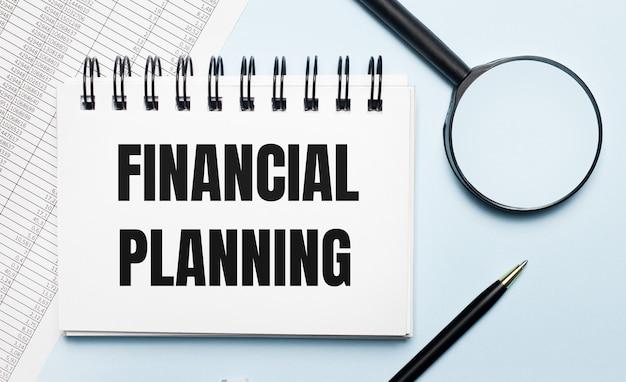 水色の背景に、レポート、虫眼鏡、ペン、および「financialplanning」というテキストが記載されたノートブック。ビジネスコンセプト。フラットレイ。