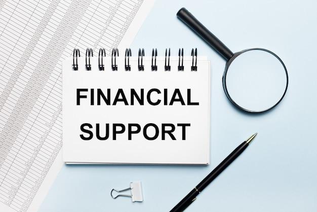 На голубом фоне отчеты, лупа, ручка и блокнот с текстом финансовая поддержка.