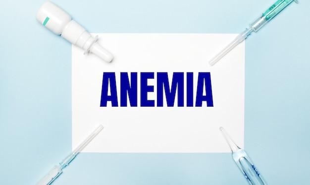 水色の背景に、注射器、薬瓶、アンプル、そして貧血のテキストが書かれた白い紙。医療の概念。