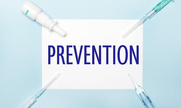 水色の背景に、注射器、薬瓶、アンプル、白い紙に「予防」と書かれています。医療の概念。
