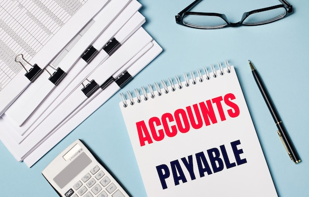 水色の背景には、ドキュメント、メガネ、電卓、ペン、および「買掛金」というテキストのノートがあります。職場のクローズアップ。ビジネスコンセプト