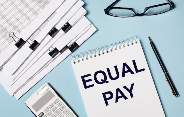 На голубом фоне - документы, очки, калькулятор, ручка и блокнот с надписью equal pay. крупный план рабочего места. бизнес-концепция