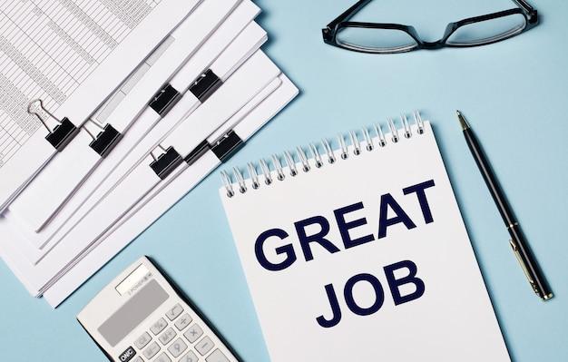 На голубом фоне - документы, очки, калькулятор, ручка и блокнот с надписью great job. крупный план рабочего места. бизнес-концепция