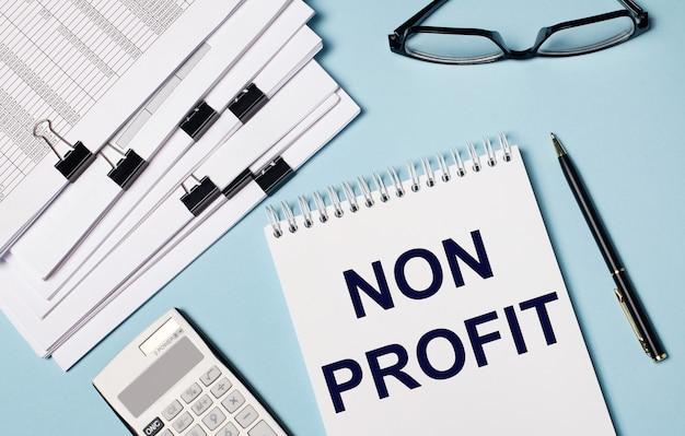 На голубом фоне - документы, очки, калькулятор, ручка и блокнот с надписью non profit. крупный план рабочего места. бизнес-концепция