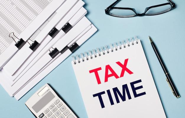 На голубом фоне - документы, очки, калькулятор, ручка и блокнот с текстом «налоговое время». крупный план рабочего места. бизнес-концепция