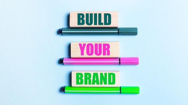 На голубом фоне три разноцветных фломастера и деревянные блоки с надписью build your brand.