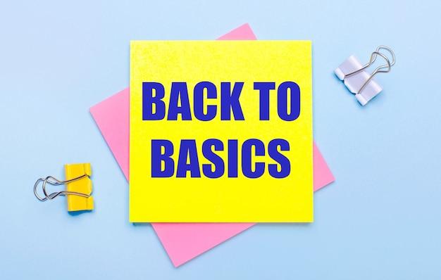 水色の背景には、黄色と白のペーパークリップ、ピンクと黄色の付箋があり、テキストは「基本に戻る」です。