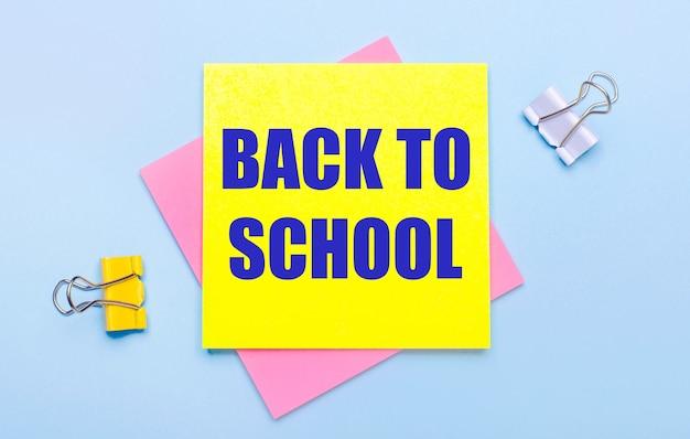 На голубом фоне желтые и белые скрепки, розовые и желтые стикеры с текстом назад в школу.