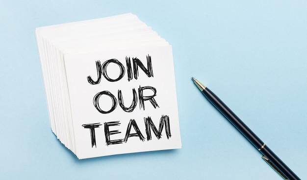На голубом фоне - черная ручка и стопка белой бумаги для заметок с текстом присоединяйтесь к нашей команде.