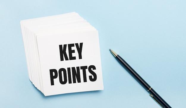 На голубом фоне - черная ручка и стопка белой бумаги для заметок с текстом ключевые моменты.