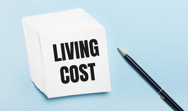 На голубом фоне - черная ручка и стопка белой бумаги для заметок с надписью стоимость проживания.