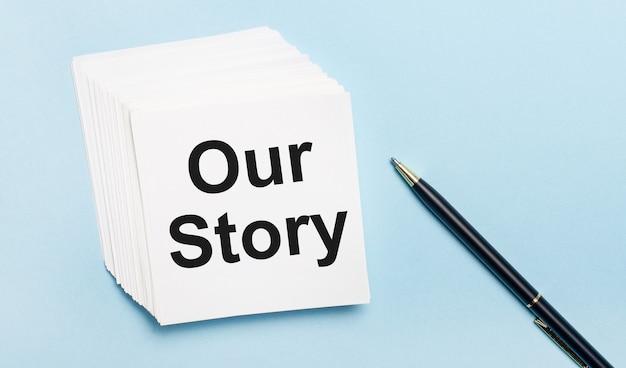 水色の背景に、黒いペンと白いメモ用紙のスタックがあり、「ourstory」というテキストが付いています。