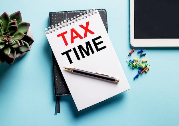 На голубом фоне - растение в горшке, планшет и еженедельник с надписью «налоговое время».