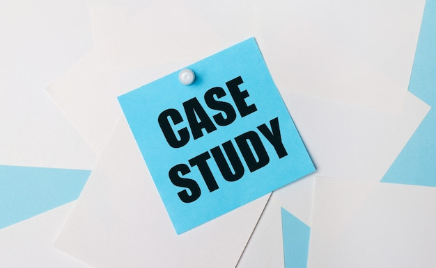水色の背景に、白い正方形の紙。白いペーパークリップを使用して、casestudyというテキストが付いた水色の正方形のステッカーを貼り付けます。
