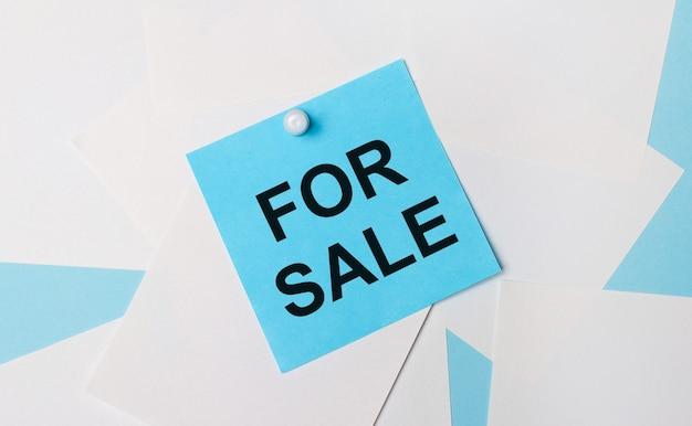 На голубом фоне белые квадратные листы бумаги. к ним с помощью белой канцелярской скрепки прикрепляется голубая квадратная наклейка с надписью «продажа».