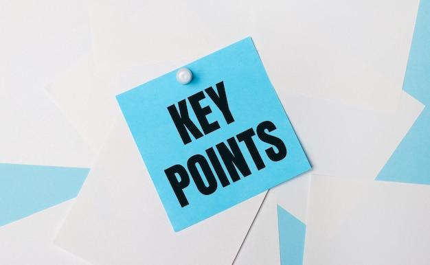 На голубом фоне белые квадратные листы бумаги. к ним с помощью белой канцелярской скрепки прикрепляется голубая квадратная наклейка с текстом ключевые точки.