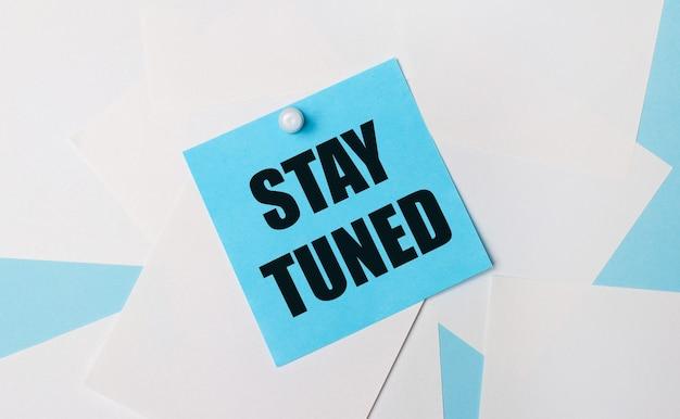 На голубом фоне белые квадратные листы бумаги. к ним с помощью белой канцелярской скрепки прикреплена голубая квадратная наклейка с надписью stay tuned.