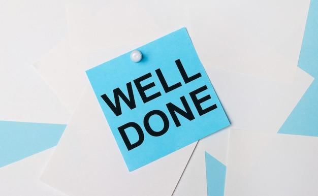 На голубом фоне белые квадратные листы бумаги. к ним прикрепляется голубая квадратная наклейка с надписью well done с помощью белой канцелярской скрепки.