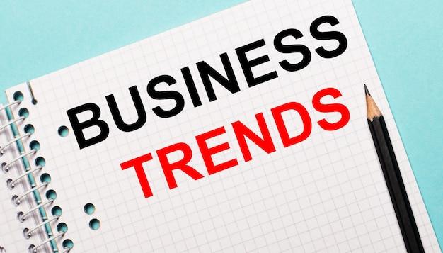 На светло-голубой поверхности клетчатый блокнот с надписью бизнес-тенденции и черным карандашом.