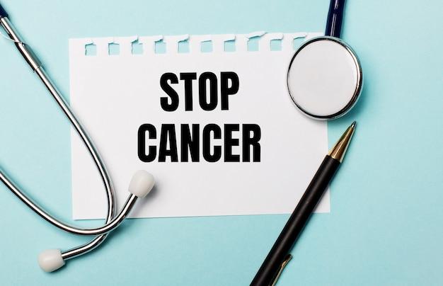 水色の表面に、聴診器、ペン、およびstopcancerと刻印された1枚の紙