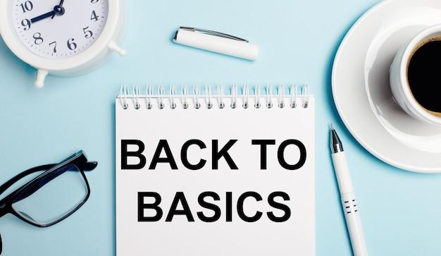 水色の表面に、コーヒーが入った白いカップ、白い目覚まし時計、白いペン、テキストが書かれたノートブックback to basics