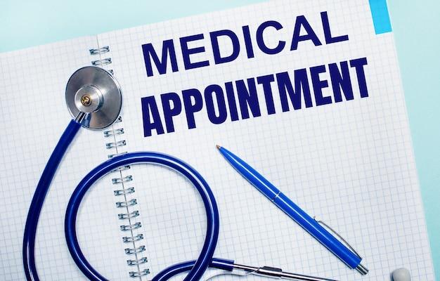水色の表面に、medical appointmentという言葉が書かれた開いたノートブック、青いペン、聴診器