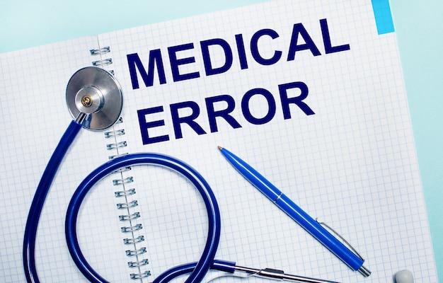 水色の表面に、medical errorという言葉が書かれた開いたノートブック、青いペン、聴診器。上から見る