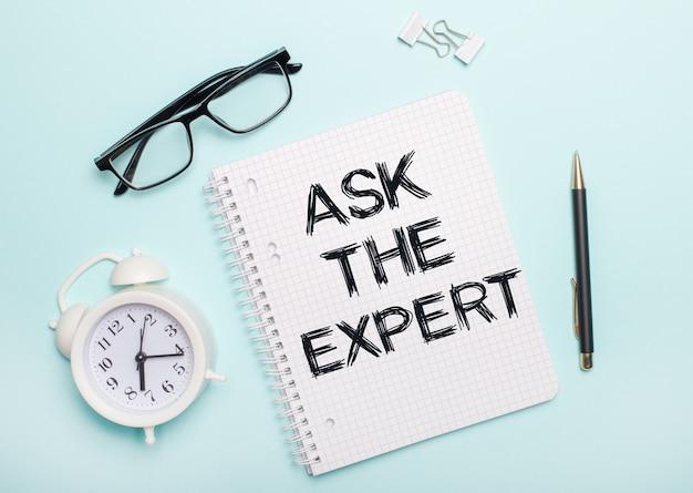 水色の表面には、黒い眼鏡とペン、白い目覚まし時計、白いペーパークリップ、ask theexpertという言葉が書かれたノートがあります。ビジネスコンセプト