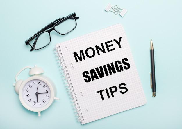 水色の表面には、黒い眼鏡とペン、白い目覚まし時計、白いペーパークリップ、そしてmoney savingstipsという言葉が書かれたノートがあります。ビジネスコンセプト
