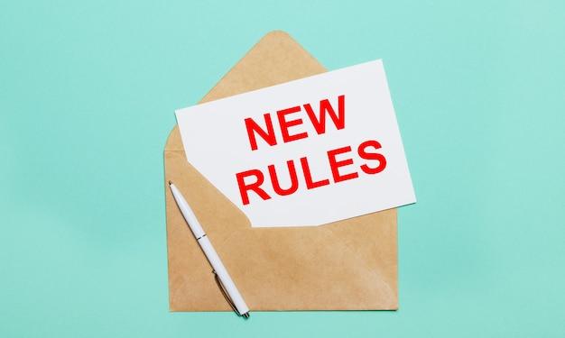 하늘색 표면에는 열린 공예 봉투, 흰색 펜 및 새 규칙이라는 텍스트가있는 흰색 종이가 놓여 있습니다.
