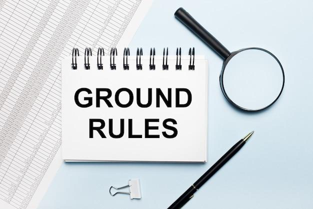 На голубой поверхности отчеты, увеличительное стекло, ручка и блокнот с текстом правила назначения. бизнес-концепция. плоская планировка.