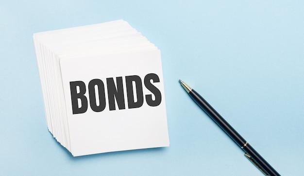 На голубой поверхности есть черная ручка и стопка белой бумаги для заметок с текстом bonds.
