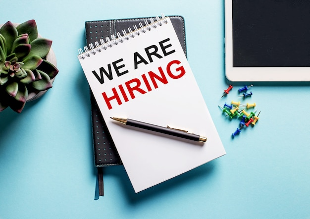하늘색 표면에 화분, 태블릿 및 we are hiring이라는 텍스트가있는 주간이 있습니다.