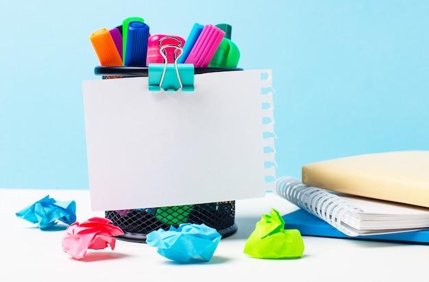 На светло-голубой поверхности подставка с яркими маркерами, блокнотами и разноцветными скомканными бумажками.