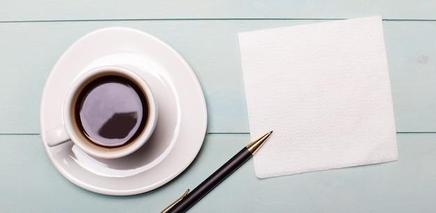 水色の木製の背景、白い一杯のコーヒー、メモ用の空のナプキン、ペン。コピースペースのある上面図