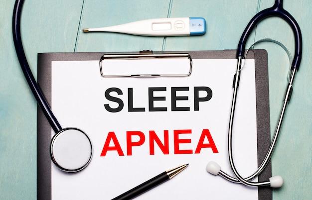 На светло-голубом деревянном фоне есть бумага с надписью sleep apnea, стетоскоп, электронный термометр и ручка. медицинская концепция