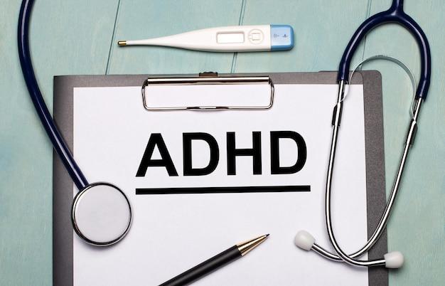 水色の木製の表面には、adhdというラベルの付いた紙、聴診器、電子体温計、ペンがあります。