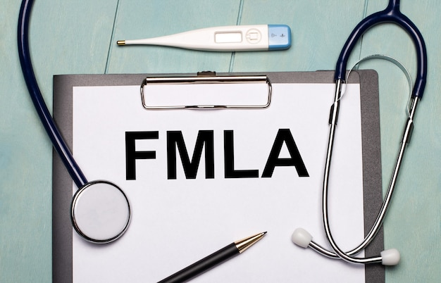 水色の木製の表面には、fmlaというラベルの付いた紙、聴診器、電子体温計、ペンがあります。