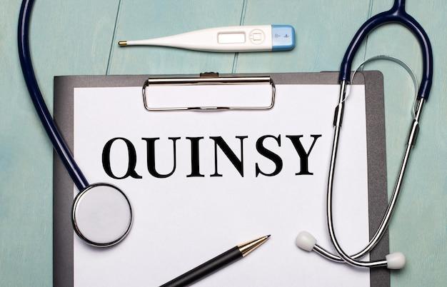 水色の木製の表面には、quinsyというラベルの付いた紙、聴診器、電子体温計、ペンがあります。