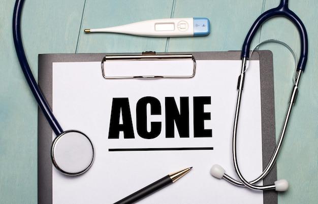 水色の木製のテーブルには、acneというラベルの付いた紙、聴診器、電子体温計、ペンがあります。医療の概念