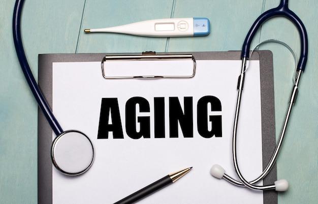 На светло-голубом деревянном столе есть бумага с надписью aging, стетоскоп, электронный термометр и ручка. медицинская концепция