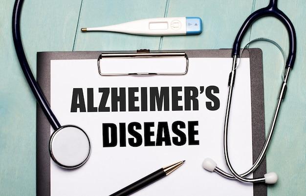 На светло-голубом деревянном столе лежит бумага с надписью «болезнь альцгеймера», стетоскоп, электронный термометр и ручка. медицинская концепция