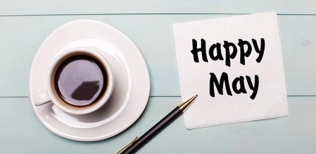 На голубом деревянном подносе есть белая чашка кофе, ручка и салфетка с надписью happy may.