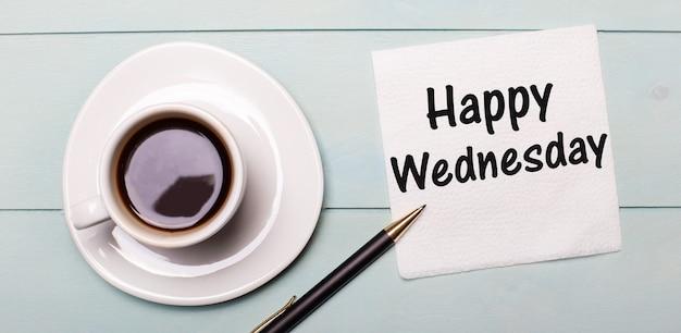 水色の木製トレイには、白い一杯のコーヒー、取っ手、そしてhappywednesdayと書かれたナプキンがあります。